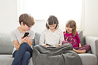 Girl sitting on the couch using mini tablet while brother and sister watching her - LVF05674