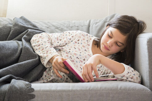 Girl lying on the couch reading a book - LVF05677