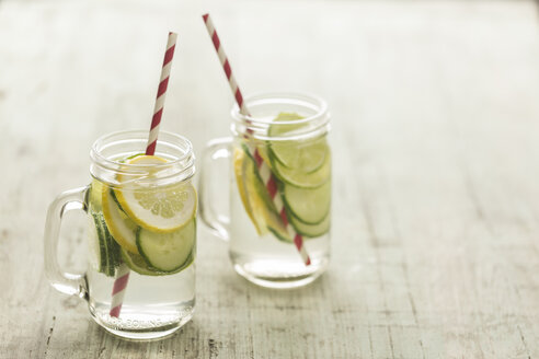 Glasses of infused water with lime, lemon, cucumber and ice cubes - JUNF00707