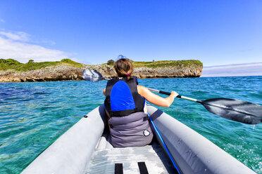 Spain, Asturias, woman kayaking at Buelna beach - DSGF01228