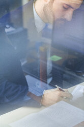 Young businessman working in office - ZEDF00453