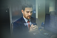 Young businessman in office behind windowpane - ZEDF00459