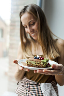 Woman preparing vegan matcha cake - VABF00893