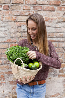 Smiling woman holding basket with fresh vegetables - VABF00902