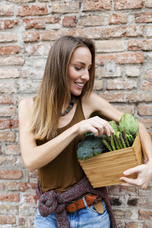 Smiling woman holding bix with fresh vegetables - VABF00905
