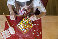 Girl garnishing gingerbread house, top view - SARF03090