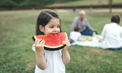 Girl eating watermelon slice with her family in background - DAPF00523