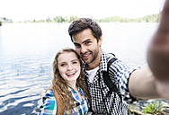 Young couple on a hiking tour at a lake taking a selfie - HAPF01180