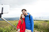 Young couple on a hiking tour taking a selfie with selfie stick - HAPF01195