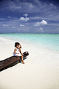 Maldives, girl sitting on a log on a beach - DSGF01244
