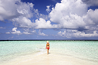 Maldives, Gulhi, woman walking on sandbank in shallow water - DSGF01250