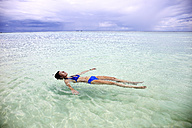 Maldives, Gulhi, woman floating in shallow water - DSGF01256