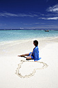 Maldives, woman sitting on beach at shallow water - DSGF01259