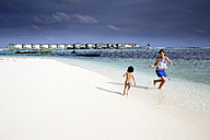 Maldives, Guraidhoo, mother and daugther playing on beach - DSGF01262