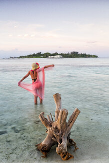Maldives, Guraidhoo, woman standing in shallow water at sunset - DSGF01265