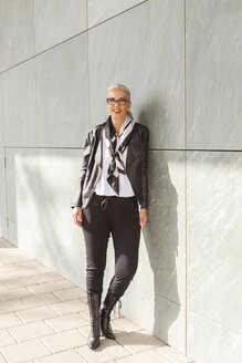 Portrait of fashionable mature woman leaning against wall - JUNF00729