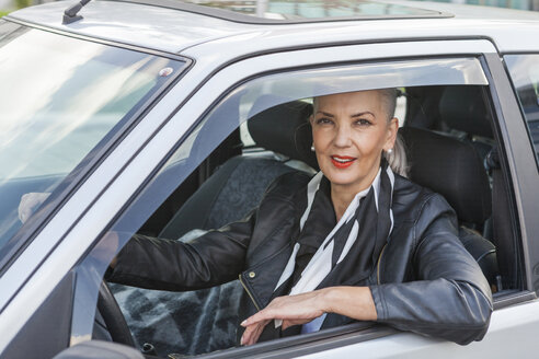 Portrait of businesswoman looking out of car window - JUNF00738