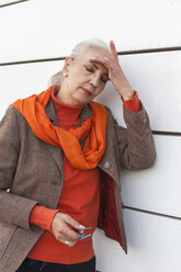 Portrait of fashionable mature woman with eyes closed leaning against white wall - JUNF00747