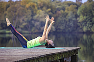 Woman practicing yoga on jetty at a lake - VTF00569