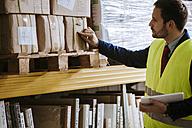 Man in warehouse supervising stock - ZEDF00463