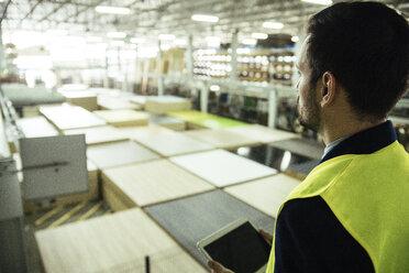 Man holding tablet overlooking warehouse - ZEDF00466