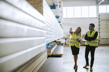Man and woman in warehouse supervising stock - ZEDF00469