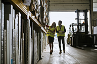 Man and woman in warehouse supervising stock - ZEDF00472
