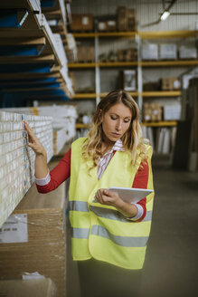 Woman in warehouse supervising stock - ZEDF00475