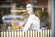 Young woman sitting in coffee shop, drinking coffee - TAMF00889