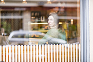 Young woman sitting in coffee shop, looking through window - TAMF00892