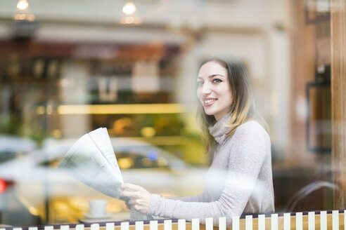 Young woman sitting in coffee shop, reading newspaper - TAMF00895