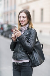 Young woman in the street using smart phone - TAMF00898