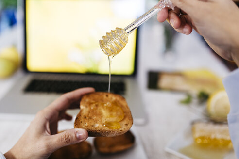 Woman dripping honey on toast at home, close-up - JRFF01106