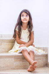 Brunette girl sitting on stairs looking up - SIPF01164