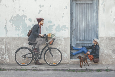 Young man on bicycle smiling at woman with dog - RTBF00558