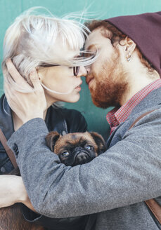 Young couple in love kissing with dog between them - RTBF00573