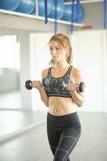 Woman training biceps in gym - JASF01384