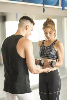 Young woman training biceps with personal trainer - JASF01387