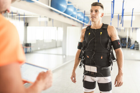 Man training with electrical muscle stimulation in gym monitored by man with tablet - JASF01405