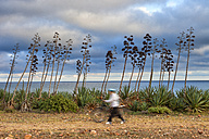 Spain, Andalusia, Natural Park of Cabo de Gata-Nijar, Playa de los Genoveses, man with bicycle passing - DSG01352