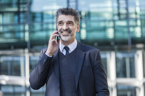 Smiling businessman outdoors on cell phone - TCF05222