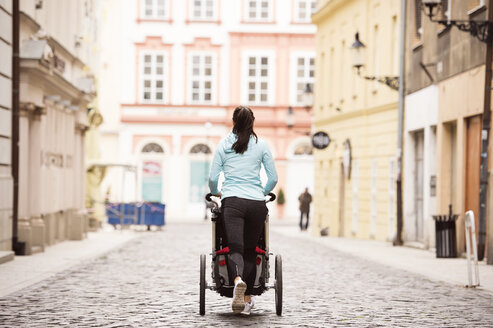 Woman running with stroller in the city - HAPF01207