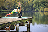 Woman practicing yoga on jetty at a lake - VTF00575