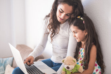 Teenage girl and her little sister using laptop - SIPF01169