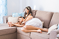 Teenage girl and her little sister lying on couch - SIPF01172