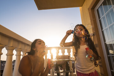 Teenage girl and her little sister blowing soap bubbles on balcony - SIPF01187