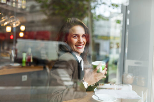 Smiling young woman in a cafe - VABF00915