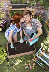 Couple preparing soil to plant vegetables in the container of their urban garden - RTBF00574