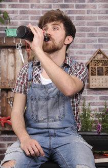Young gardener taking a break drinking beer - RTBF00583