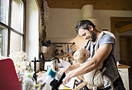 Happy father with baby in baby carrier doing the dishes - HAPF01224